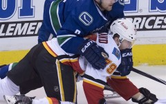 Vancouver Canucks defenceman Yannick Weber (6) fights for control of the puck with Calgary Flames left wing Michael Ferland (79) during the first period of game 2 of the NHL Western Conference first round playoff hockey series in Vancouver, B.C. Friday, April 17, 2015. The Canucks have re-signed defenceman Weber to a one-year deal.THE CANADIAN PRESS/Jonathan Hayward